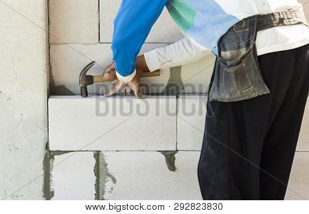 close up worker bricklayer install brick and adjust with hammer poster