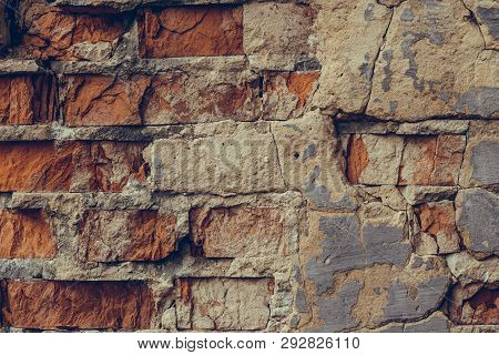 Red Brick Wall In The Cracks. Shattered Brick Wall Close Up. Old Ruined Brick Wall. Dilapidated Bric