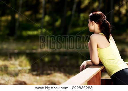 Young woman is sport outfit resting on heandrail and looking on nature.