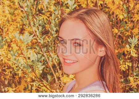Portrait of young woman in the blooming garden in the spring time.