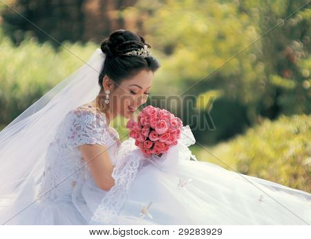 Beautiful Asian bride in semi formal gown with bouquet of wild flowers