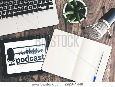 Top View Of Podcast Recording Equipment On Wooden Desk With Podcast Logo On Tablet Screen
