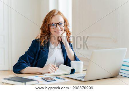 Successful Economist In Eyewear, Checks Information On Laptop Computer, Reads Information On Financi