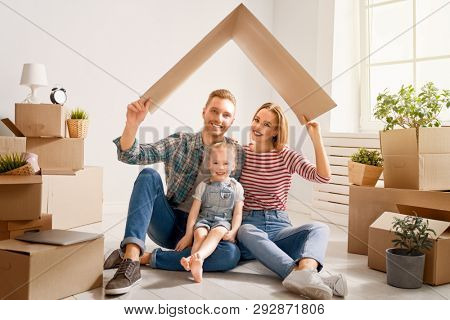 Concept of housing for young family. Mother, father and child girl in new house with a cardbox roof. Symbol of protection and property.