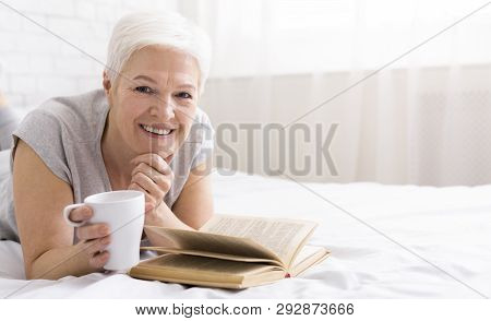 Smiling Senior Woman Lying On Bed With Book And Drinking Coffee, Enjoying Free Retirement Time, Free