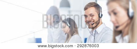Call Center Worker Accompanied By His Team. Smiling Customer Support Operator At Work. Young Employe