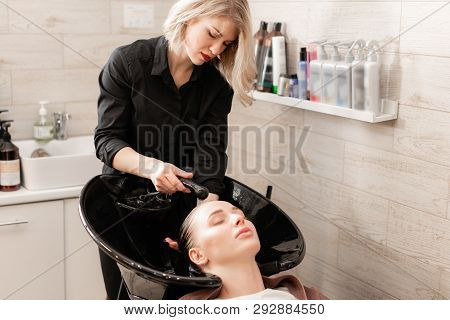 Beautiful Girl Washes Her Hair Before A Haircut In A Beauty Salon. Hair Washing At A Hairdressing. P