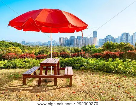 Garden wooden table set under red sunshade in the park,with city Skyline in background.View from a hill in the niugangshan park,Fuzhou,Fujian,China