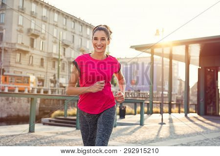 Smiling sporty woman running outdoors. Latin young woman jogging in the city street at susnset. Happy fitness girl wearing sportswear and exercising outdoor.