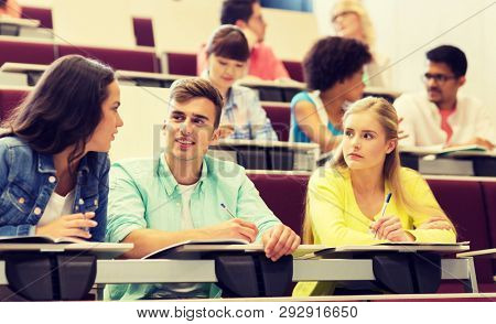 education, high school, university, learning and people concept - group of international students with notebooks writing in lecture hall