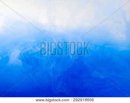 Drop Of Blue Paint Dissolving Into Water, Close Up View. Abstract Background. Acrylic Clouds Swirlin