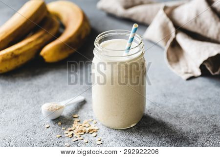 Protein Banana Smoothie In Jar, Protein Scoop, Oats And Linen Textile On Table. Healthy Vegan Or Veg