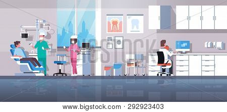 Dentist With Assistant Drilling Teeth Of Man Patient Lying In Dentistry Chair Professional Dental Of