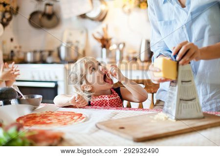 Family Cooking Pizza In Kitchen. Mother And Daughter Preparing Homemade Italian Food. Funny Little G
