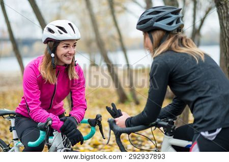 Two Young Smiling Female Cyclists with Road Bicycles Resting and Having Fun in the Park in the Cold Autumn Day. Healthy Lifestyle Concept.