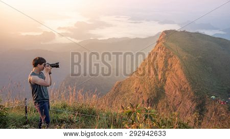 Young Asian Male Photographer And Traveler Taking Photo Of Mountain Landscape Scenery During Sunrise