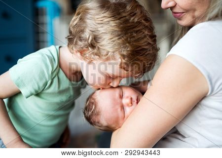 A Small Boy Kissing A Sleeping Newborn Baby Brother At Home.