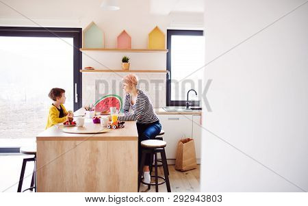 A Young Woman With A Small Daughter Spending Time Together In A Kitchen.