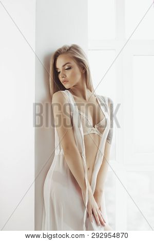 Sensual Attractive Blonde Woman Posing Indoors Near The Window Wearing Sexy Lingerie, Looking Down.