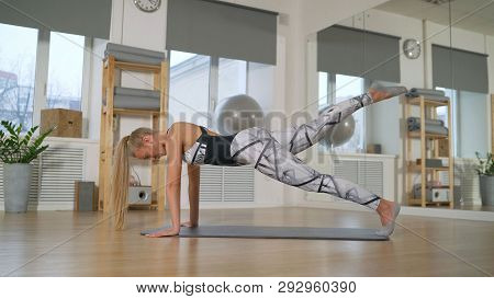 The Girl Shows The Pilates Exercise. Pilates In The Sports Hall. The Girl Is Engaged In Pilates. The