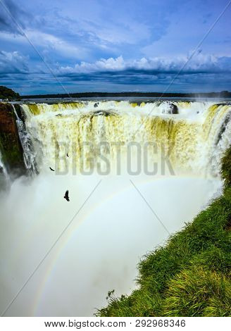 Andean condors fly above the roaring water. /The Garganta del Diablo/ Devil's Throat is the most grandiose part of the Iguazu Falls on the Parana River. Concept of active and extreme tourism