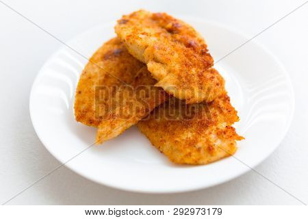 Bread crumb coated fried chicken breast on a white plate