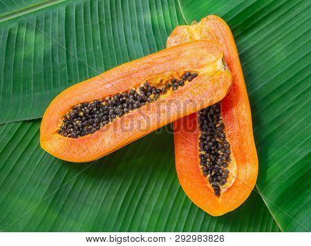2 Halves Of Fresh Raw Exotic Tropical Thai Fruit Carica Papaya On Banana Leaves, Top View