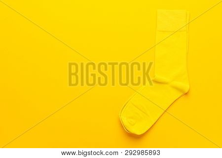 Pair Of Socks On Bright Yellow Background. Top View Of Yellow Socks With Copy Space. Minimalist Phot