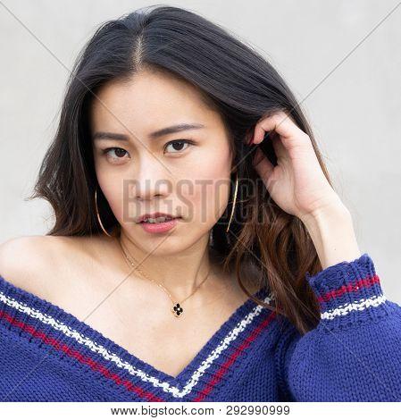 Beautiful smiling Asian woman wearing knit sweater off shoulder.