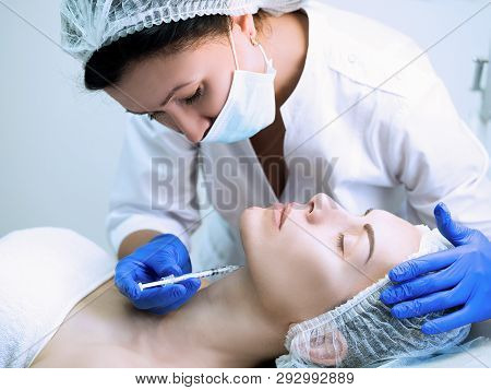 Beauty Injection. Cosmetician In Parlour With Head Of Patient And A Disposable Syringe In Hand. Clie