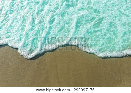 White Foam On A Sandy Beach With Copy Space.soft Wave Of Blue Ocean.