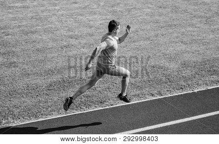 Athlete Run Track Grass Background. Sprinter Training At Stadium Track. Runner Captured In Midair. S