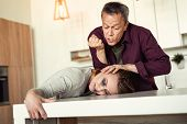 Angry furious adult man attacking helpless wife in kitchen poster