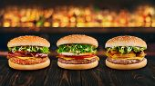 three burgers at brown wooden tabletop with blurred bar at backdrop . Fastfood concept with hamburgers at wooden table. poster