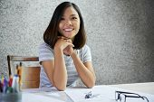 Portrait of young beautiful construction engineer sitting at table in construction bureau poster