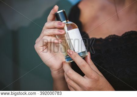 Perfume Bottle Of A Female Hand. Young Stylish Woman Holding A Bottle Of Perfume. Fashionable Perfum