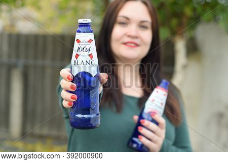 Young Girl Holds 1664 Kronenbourg Blanc Beer Glass Outdoors. 1664 Blanc Is The Wheat Beer From The F