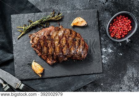 Grilled Flat Iron Steak On A Stone Board, Marbled Beef. Black Background. Top View