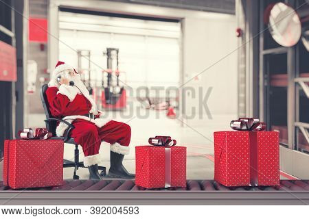 Santa Claus Busy With The Orders Of Christmas Gifts In A Warehouse