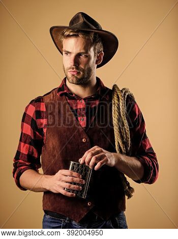 Sheriff Concept. Brutal Cowboy Drinking Alcohol. Man Handsome Cowboy Beige Background. Western Life.