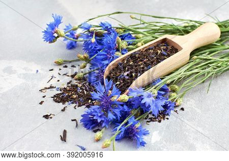Black Tea Mix With Dried Cornflower Petals And Thyme In Wooden Scoop, Fresh Cornflowers Bouquet.