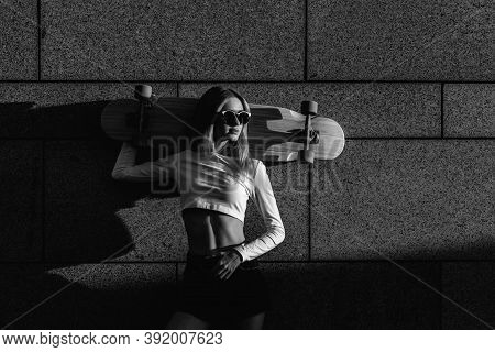 Black-white Portrait Of A Young Woman With A Longboard.