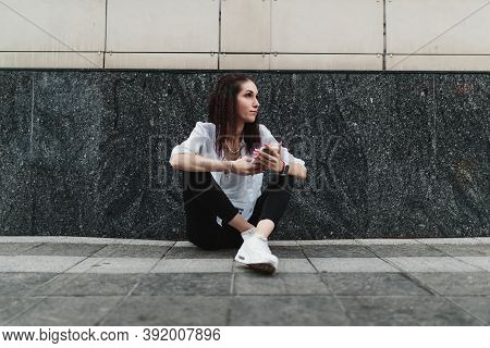 Woman Uses The Phone While Sitting On The Ground.