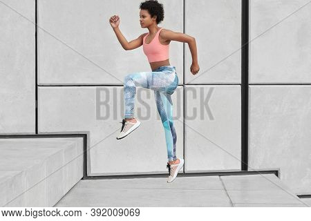Sideways Shot Of Athletic Woman Looks Ahead, Runs Up Stairs, Wants To Loose Weight, Has High Jump, W
