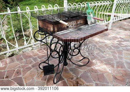 Barbecue Grill In The Backyard Outside. Empty Dirty Kitchen Equipment After Cooking Dinner. Black Gr