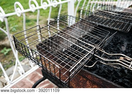 Closeup View At Barbecue Grill In The Backyard Outside. Empty Dirty Kitchen Equipment. Black Grill W