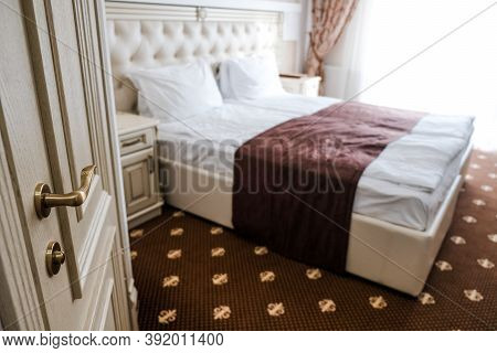 Luxury Hotel Room On A Tourist Retreat. Entering The Suite, Door Open And Bed In The Background. Ele