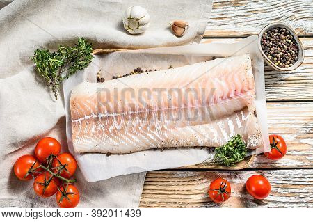Fresh Raw Cod Loin Fillet With Thyme. White Wooden Background. Top View