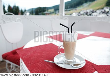 Glass Cup Of Coffee Latte With Two Plastic Straws On A Table Outside. Serving Caffeinated Drinks In