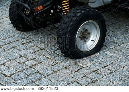 Deflated Tire Of 4x4 Quad Bike On A Pavement. Off Road Vehicle With Flat Tire After A Dangerous Ride